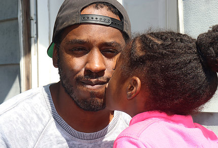 Black man in cap is kissed by young girl