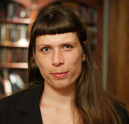 Agnes Karasik in front of a book-lined bookshelf