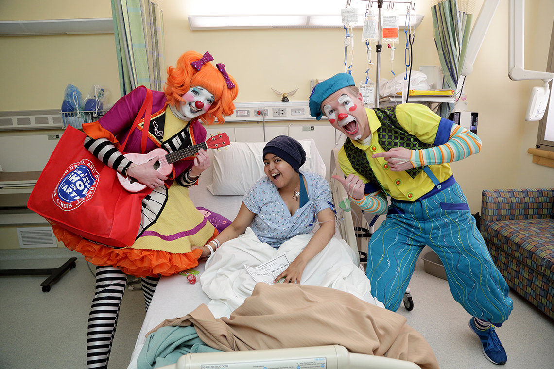 Clowns visit patient in her bed.