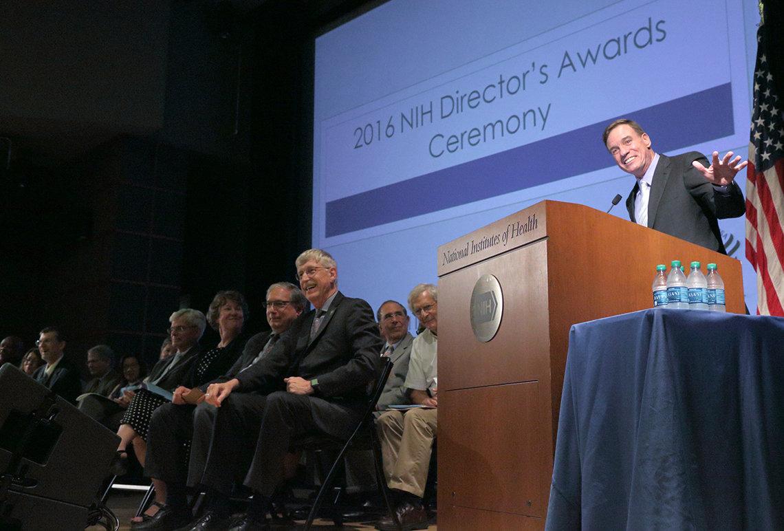 Sen. Warner gestures at podium.