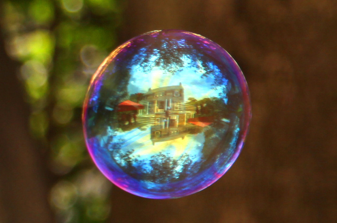 Soap bubble reflects Stone House.