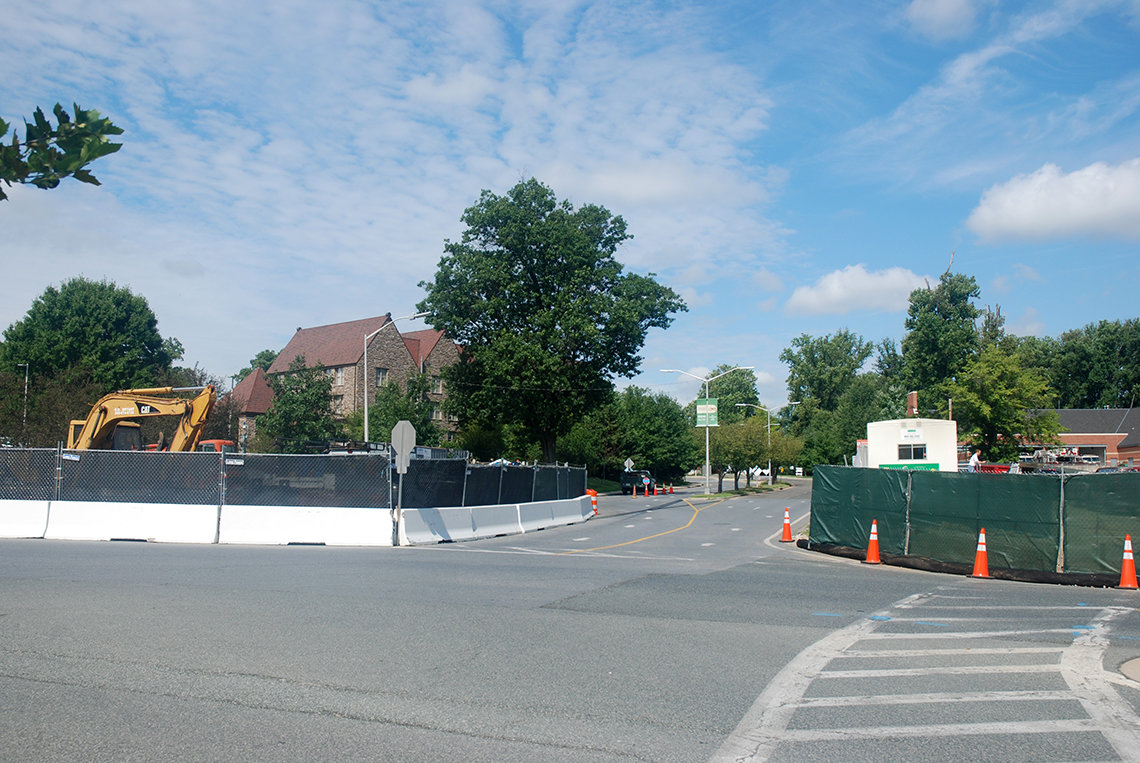 Portion of road fenced in with white concrete barriers