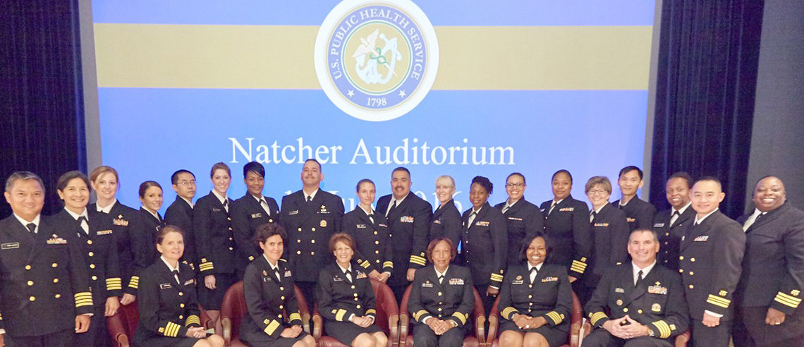 Large group of Commissioned Corps members in front of slide announcing promotion ceremony