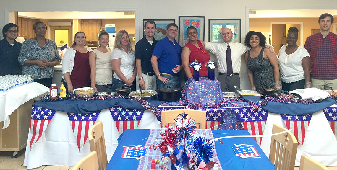 Large group of people face the camera behind a table adorned with patriotic quilt