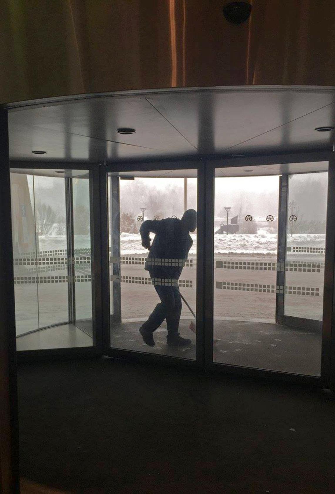 A snow shoveler clears a hospital entrance