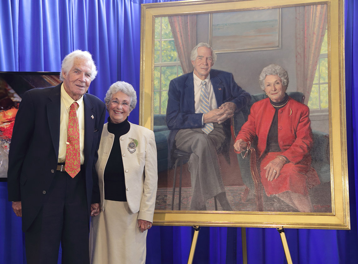 Dr. and Mrs. Lindberg stand by a portrait of themselves.