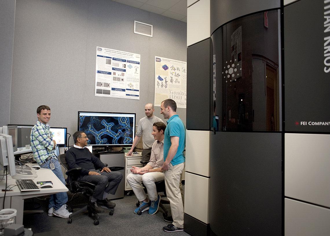 Subramaniam and his team gather around the microscope.