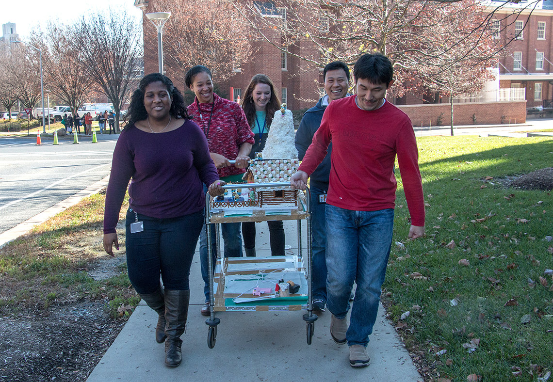 Group carries gingerbread house to contest.