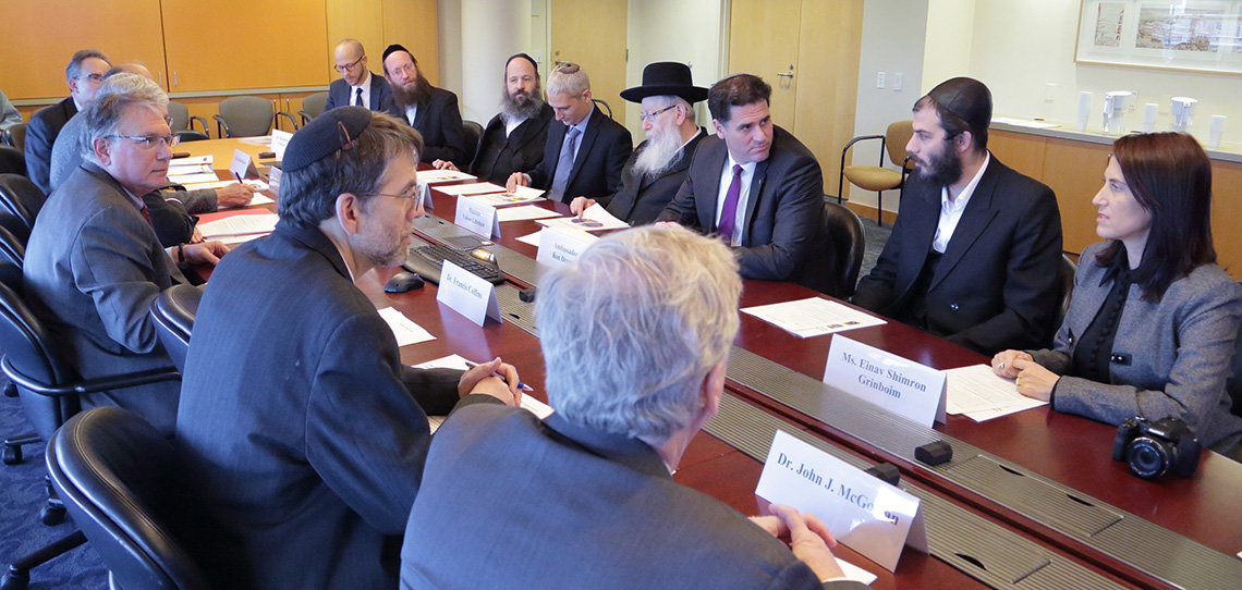 The Israeli delegation and NIH leaders sit around a board room table.