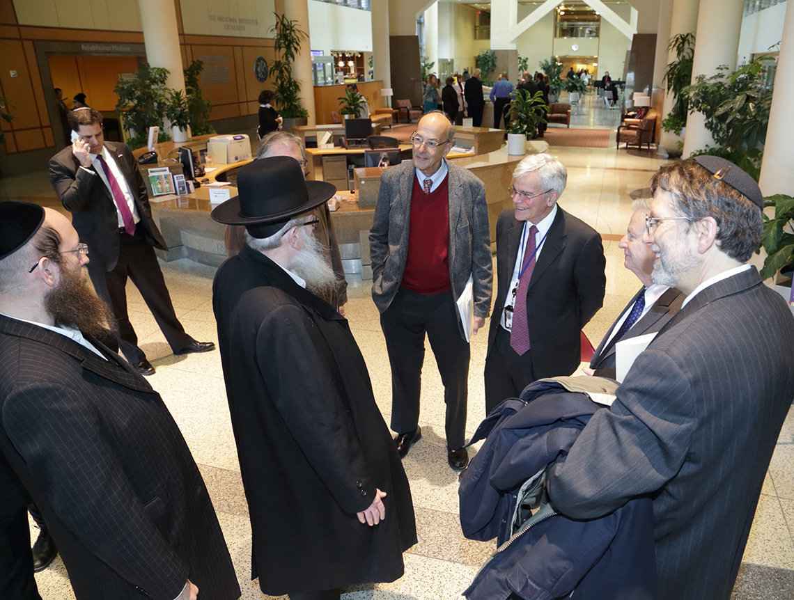 Litzman talks with NIH leaders in Clinical Center atrium.