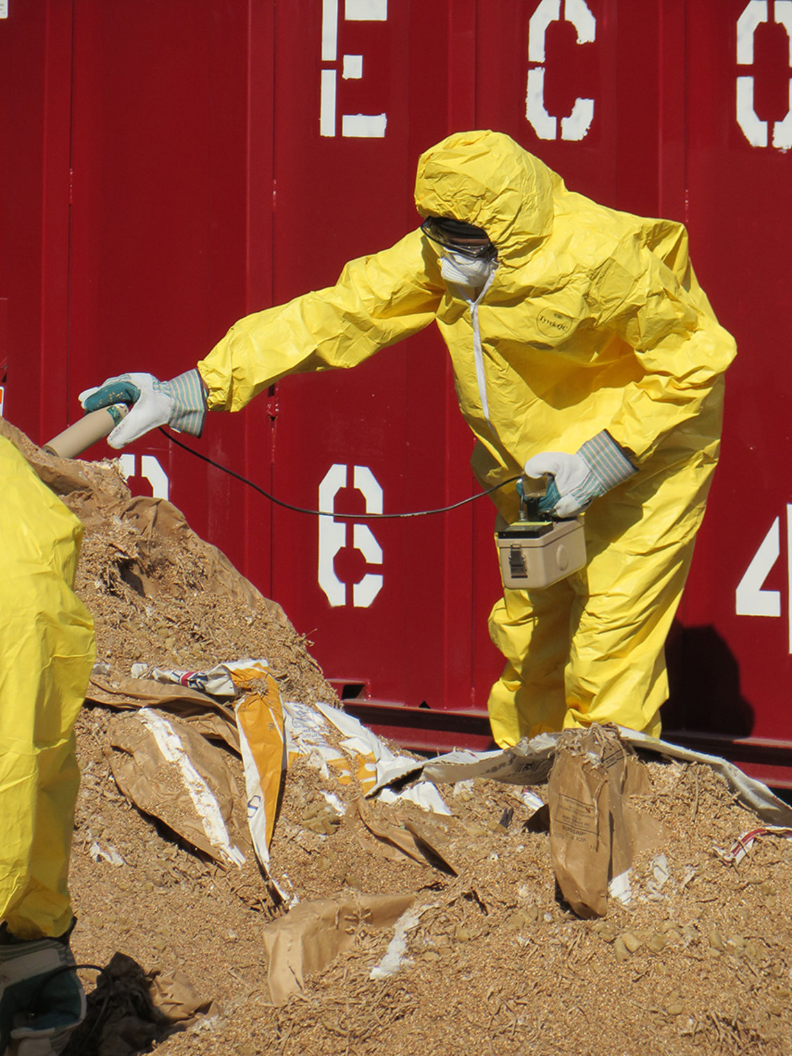 Person in hazmat suit, mask and gloves working on pile of dirt, landfill