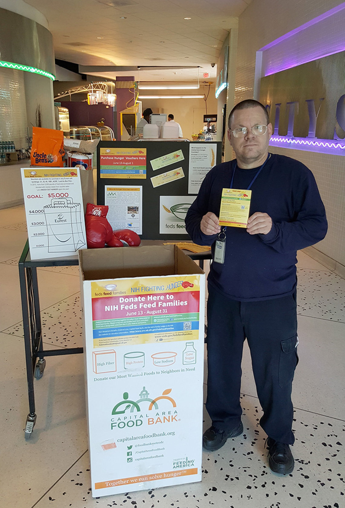 Harrison stands in cafeteria holding hunger-fighting campaign information.