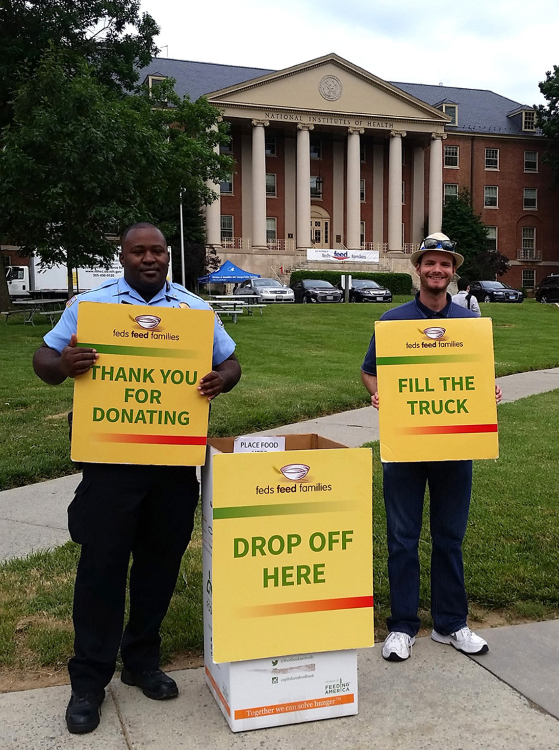 NIH employees hold yellow signs that read: fill the truck, thank you for donating, drop off here in front of Bldg. 1.