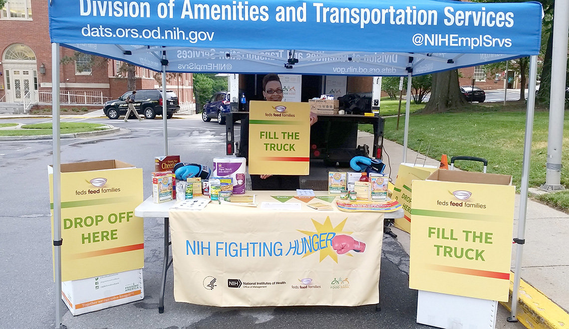 NIH'er stands by drop-off bins under blue DATS tent holding a Fill the Truck sign