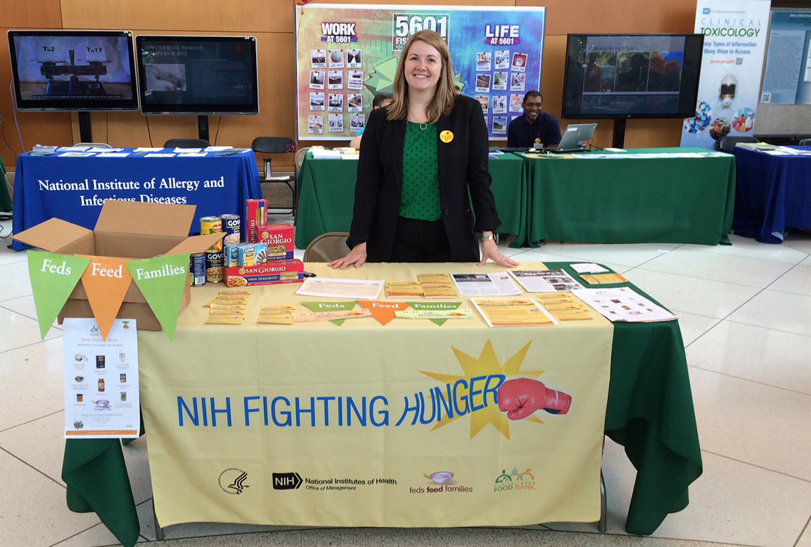 Welcher stands at NIH Fighting Hunger information table in the CC south lobby