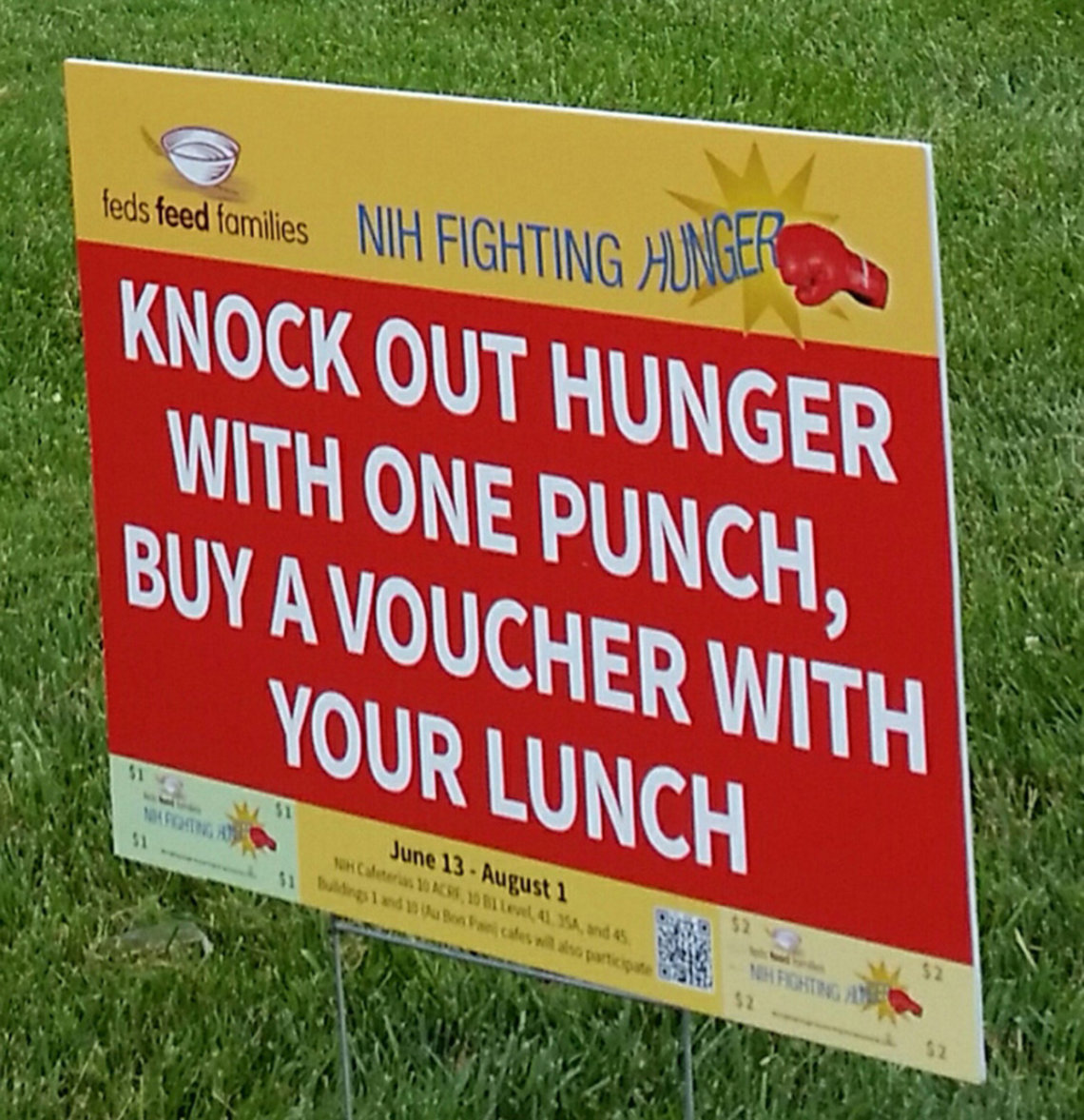Red sign on lawn reads: knock out hunger with one punch, buy a voucher with your lunch.