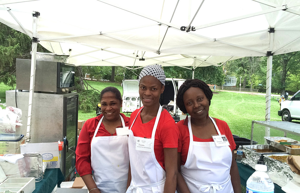 Ladies serve food at event.