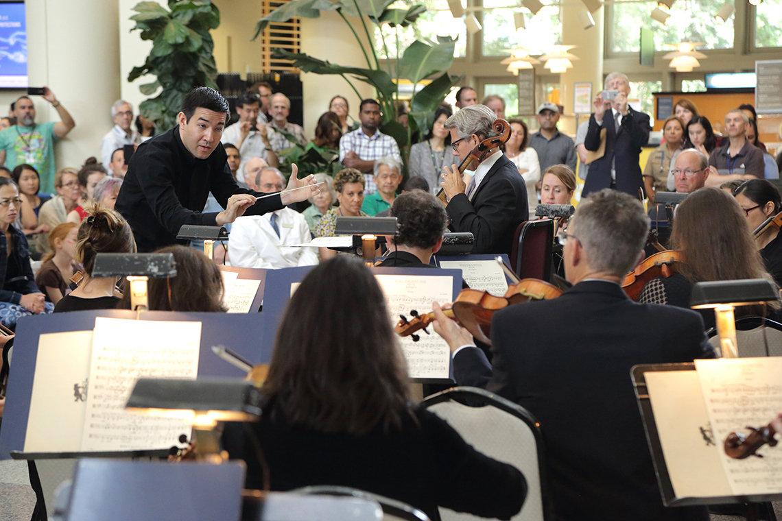 Conductor leads orchestra as NIH director looks on.