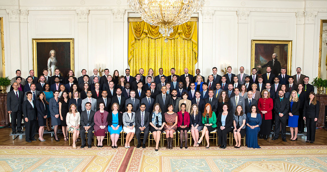 President in large group photo with scientists