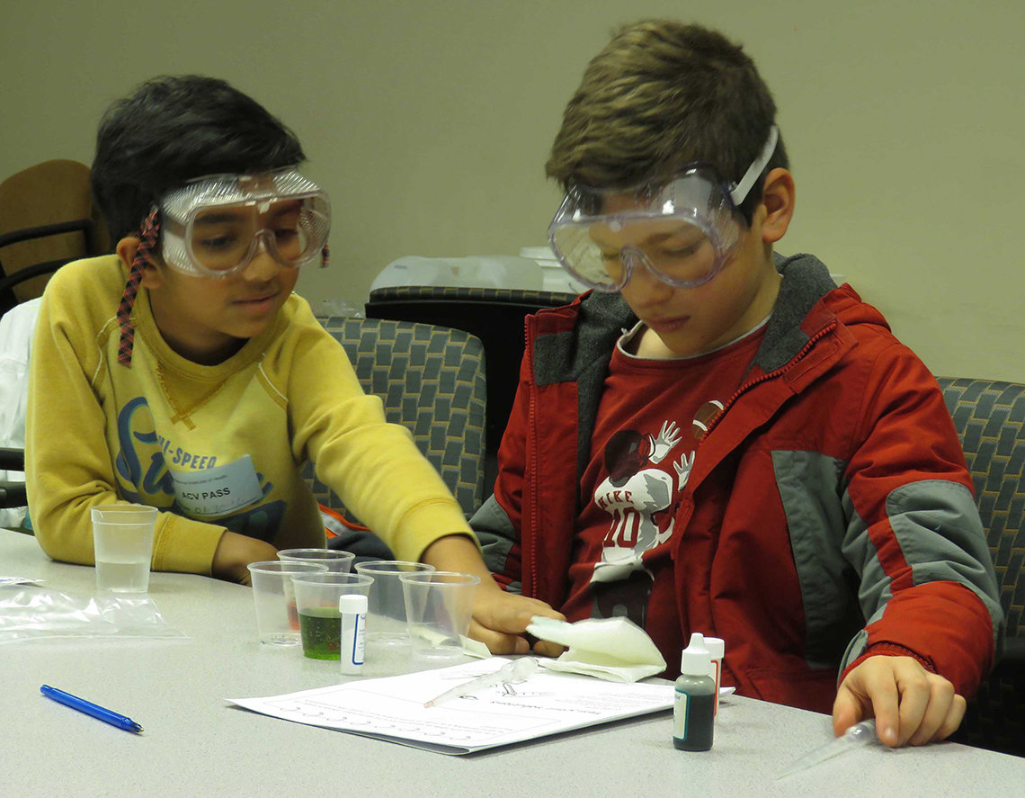 Two kids wear goggles and conduct an experiment