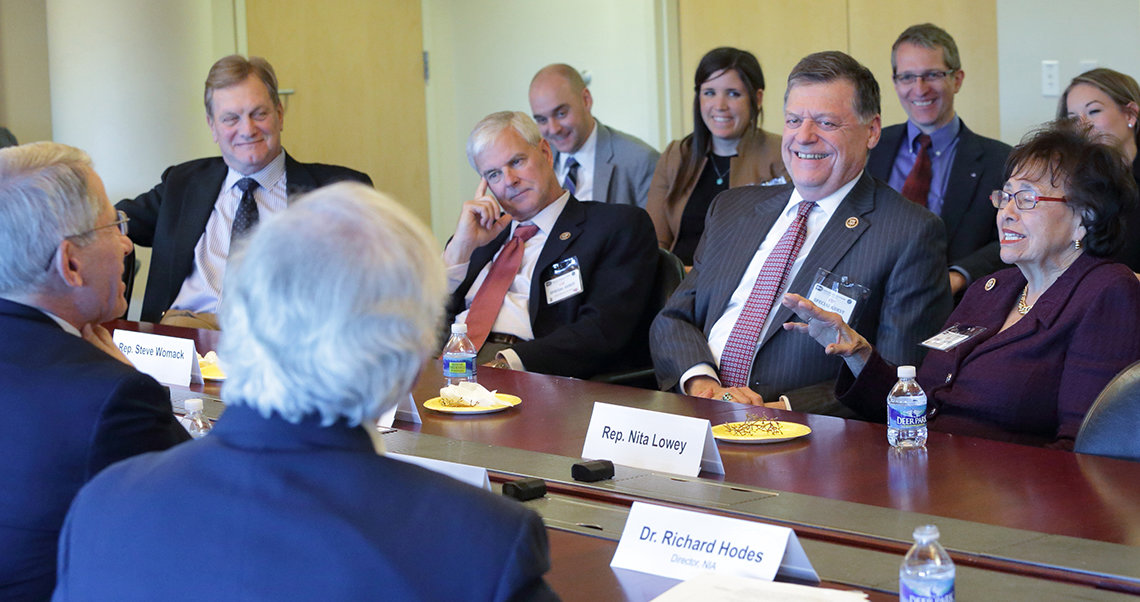 Visiting members of Congress sit, talking around board room table.