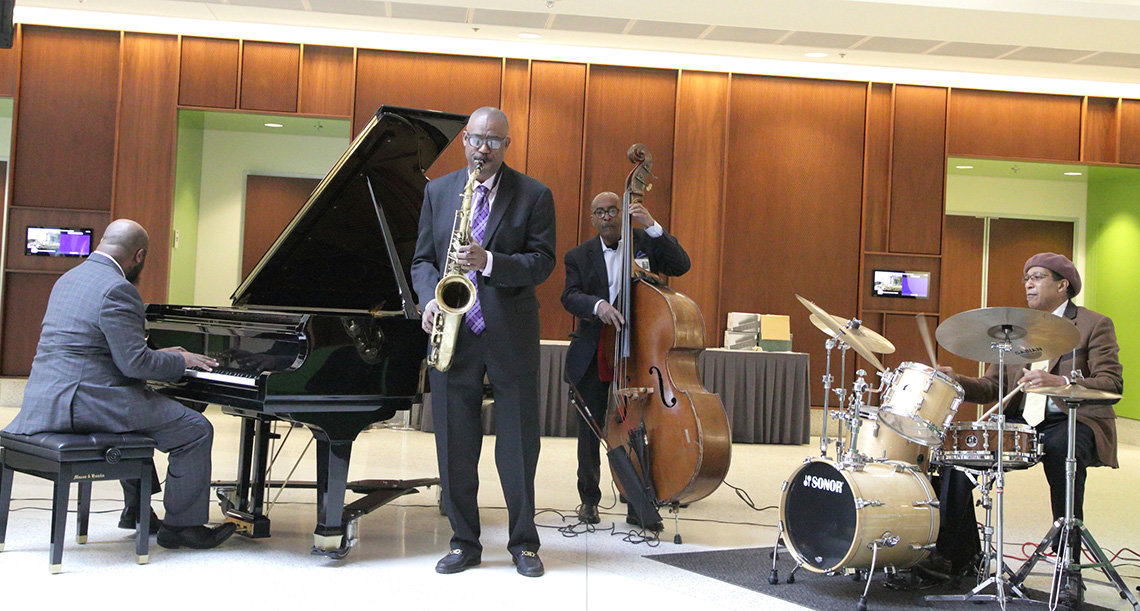 Jazz musicians playing piano, saxophone, upright bass and drums