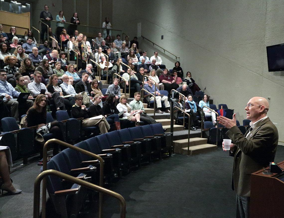 Rosenstein stands talking to audience in Lipsett Amphitheater.
