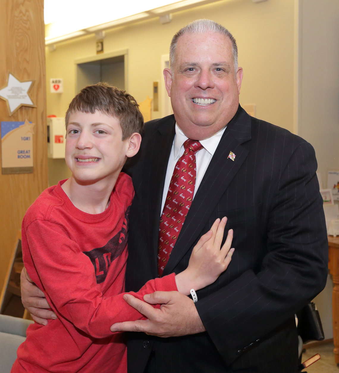 Hogan hugs young patient