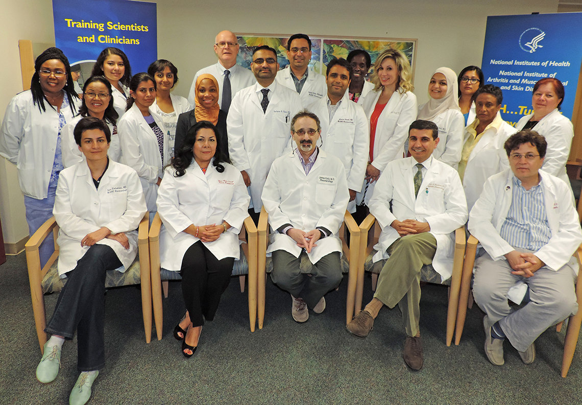 NIAMS staff, all in white lab coats, pose together.