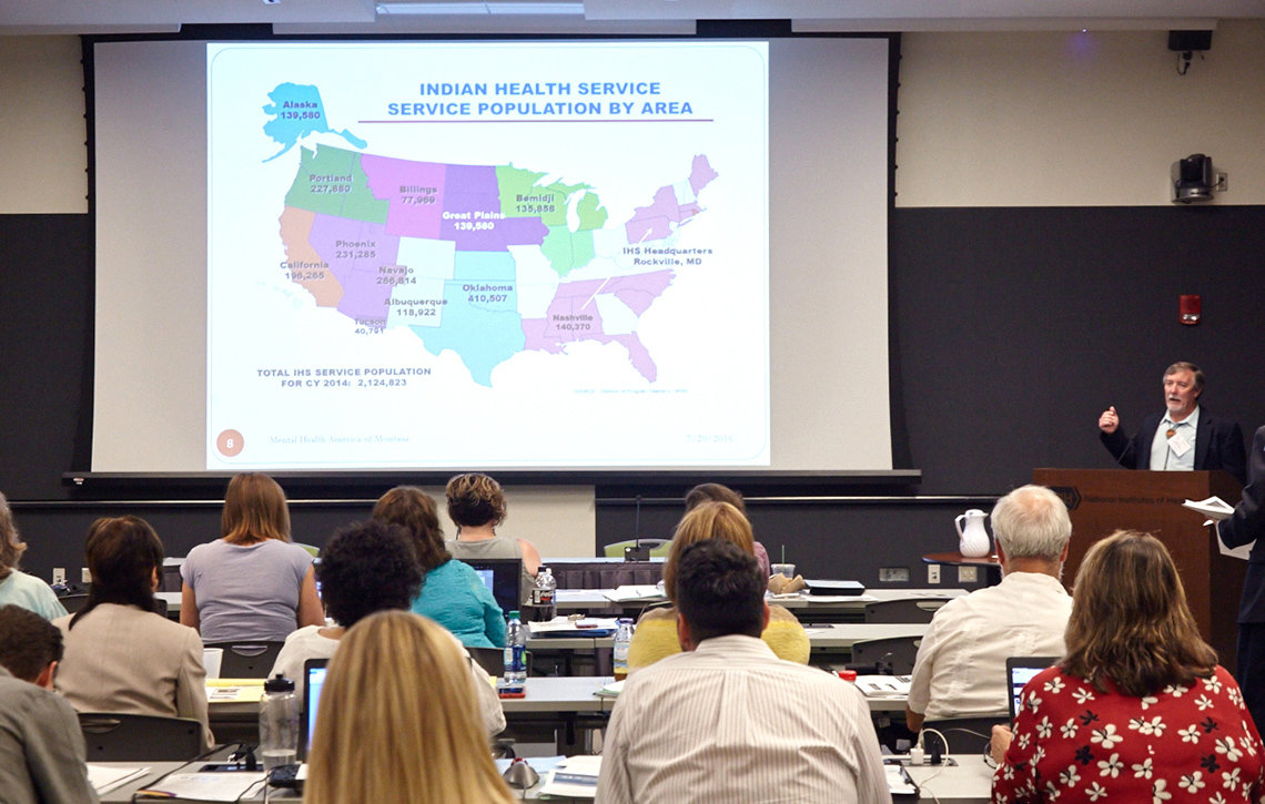 Dan Aune speaks to audience pointing to colorful slide of U.S. map from the Indian Health Service