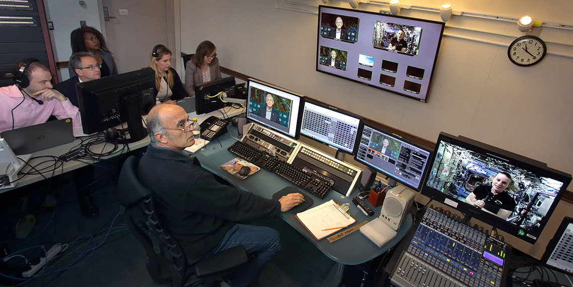 Staff utilize sound board, several computers and monitors and other equipment.