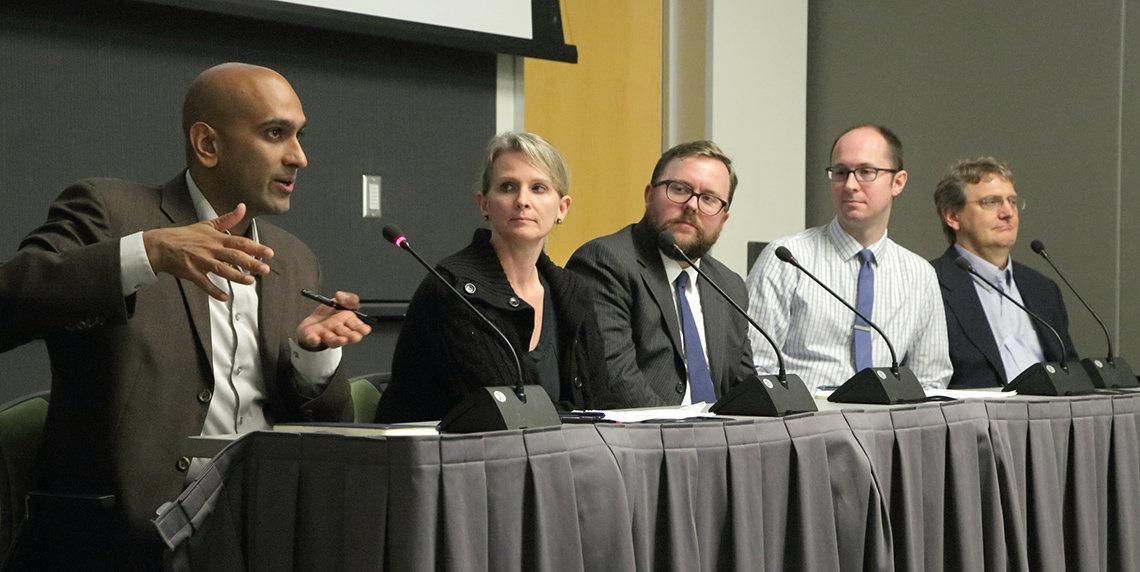 Seated at table, Patel speaks as panelists look on