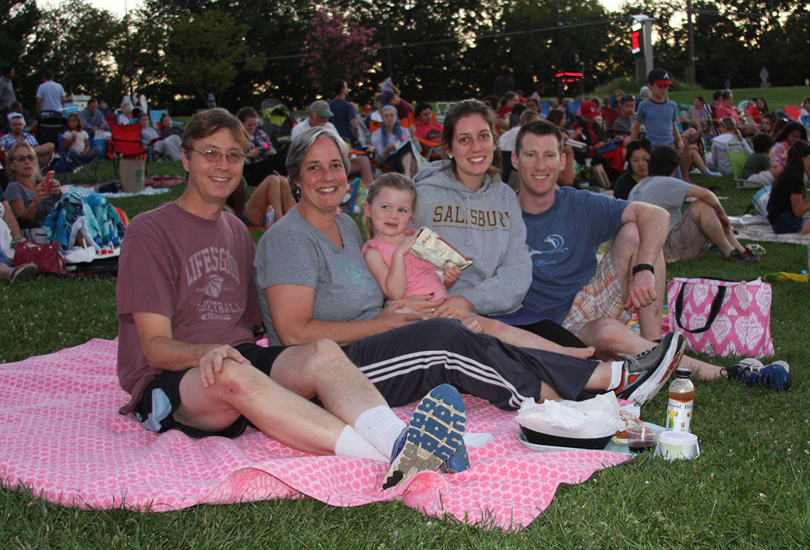 Family sits on pink blanket on the lawn, ready for the movie.