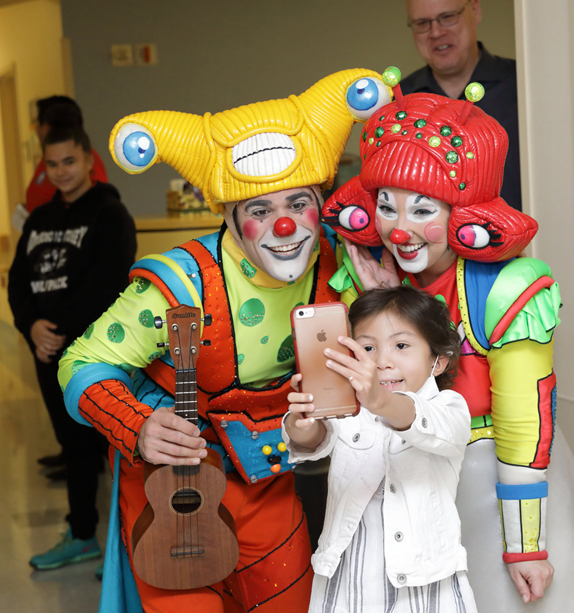 Young girl takes a selfie with circus clowns.