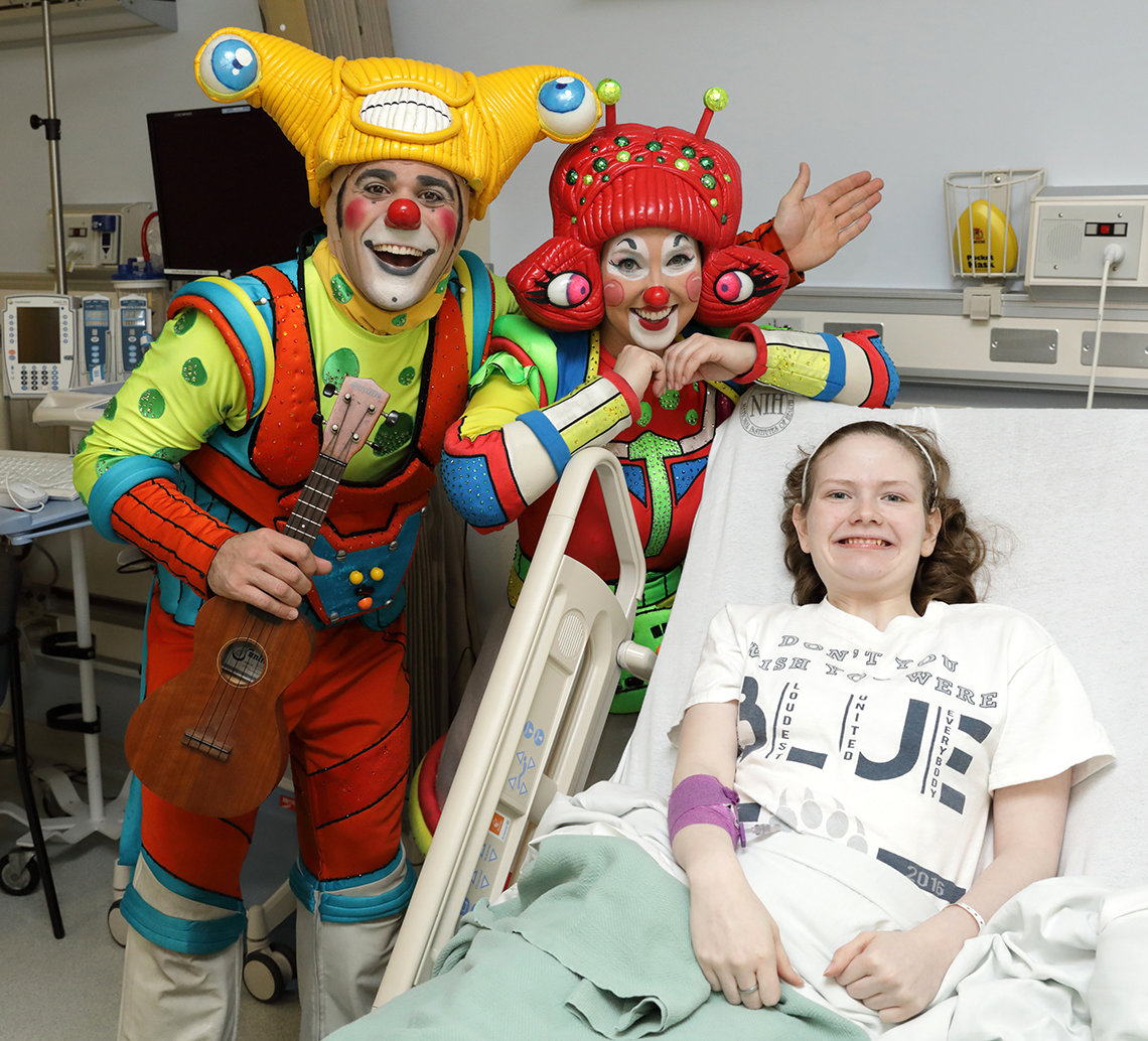 Young girl in hospital bed smiles as clowns pose beside her.