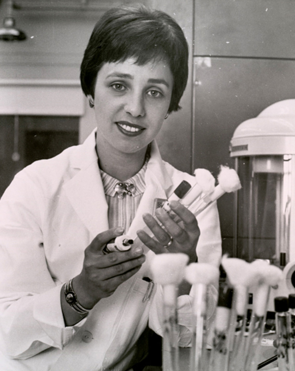 Dr. Maxine Singer holds test tube vials in the lab