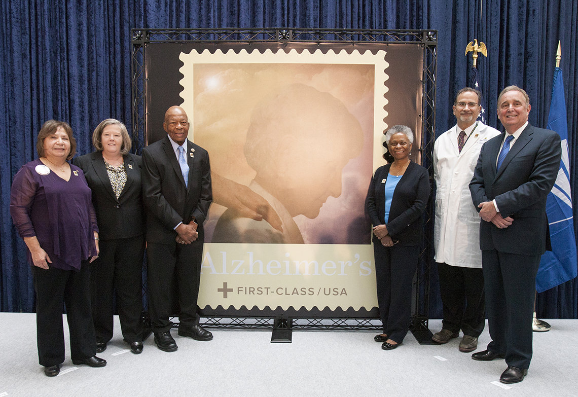 Group stands next to stamp image.