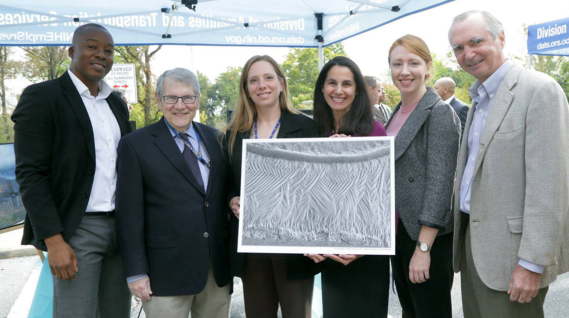 NIAMS colleagues hold art submitted in the IC directors art challenge.