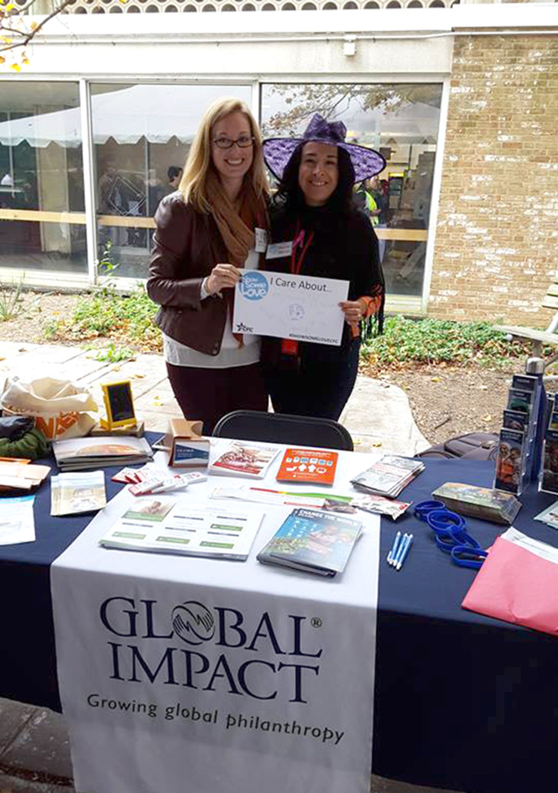 Two employees from Global Impact staff an information table.