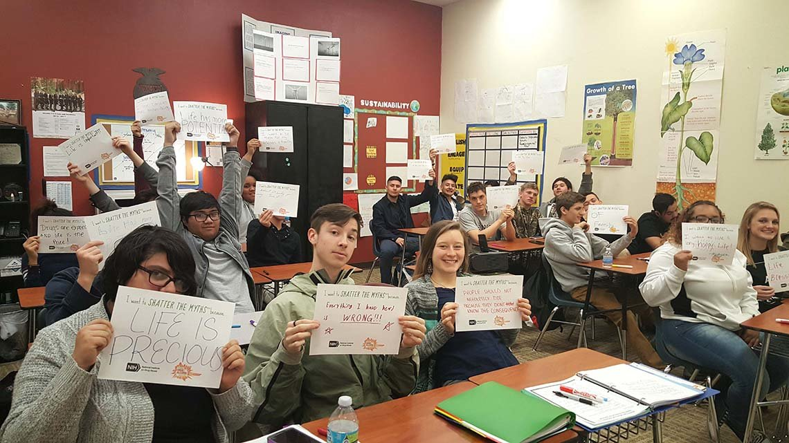 "Teens hold up ""shatter the myths"" pledge cards."