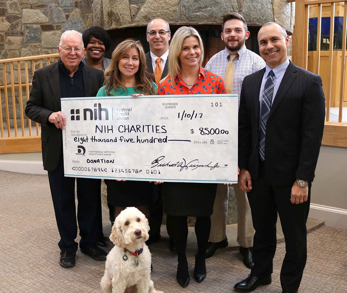 Several people hold up a large check made out to NIH Charities