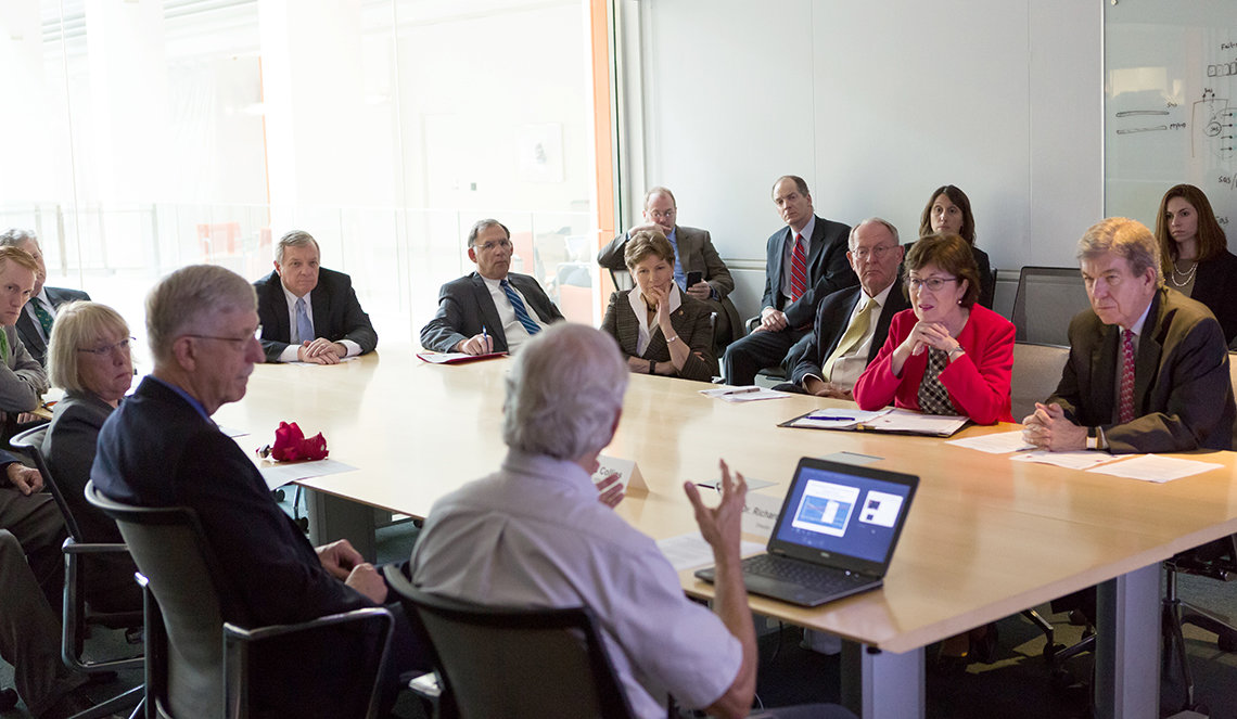 Hodes briefs a group sitting at a conference table
