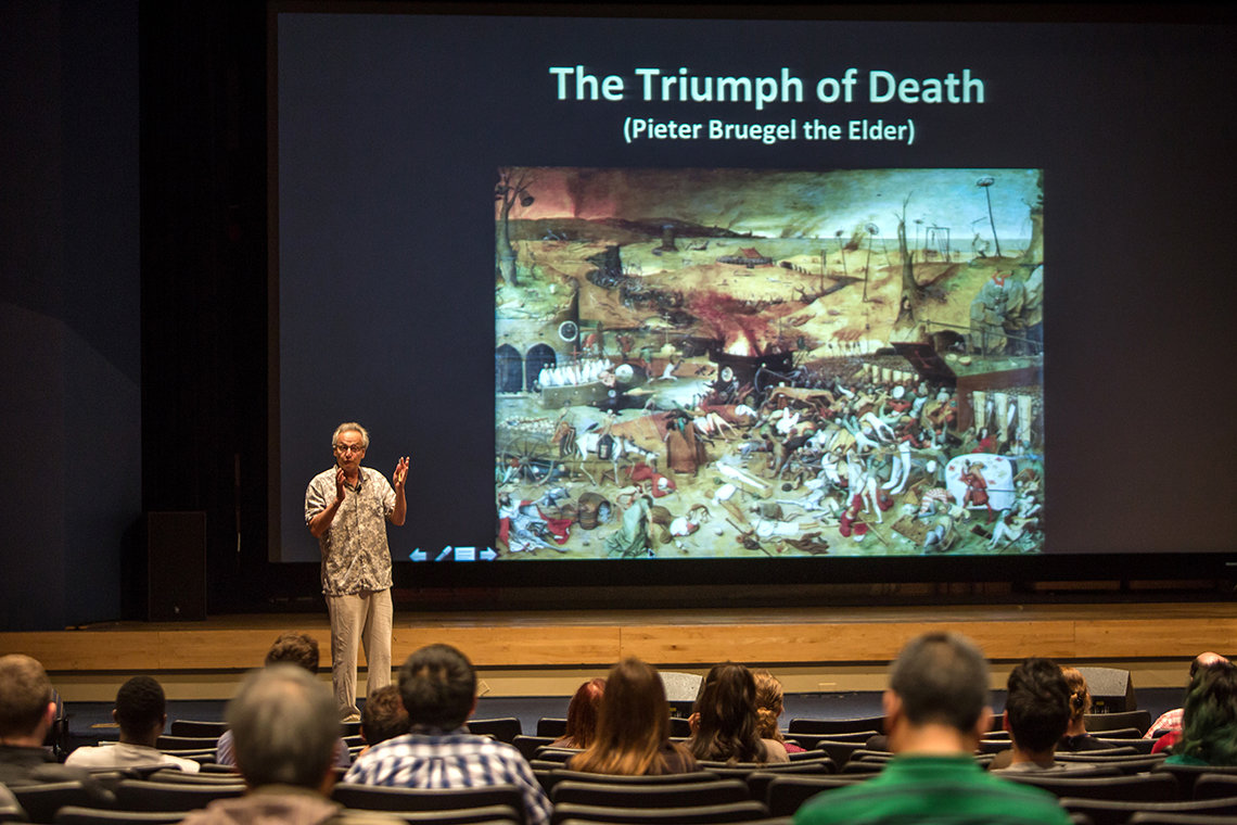 Kolter speaks in front of a slide featuring the painting, The Triumph of Death