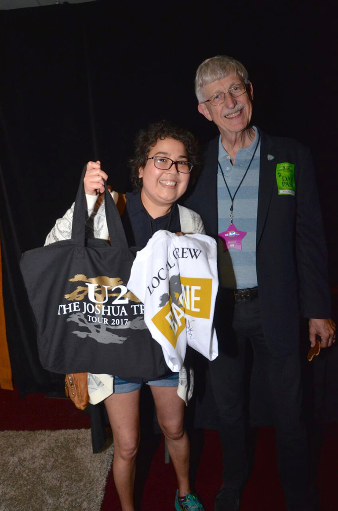 Ness  holds up a tote bag and a t-shirt with Collins