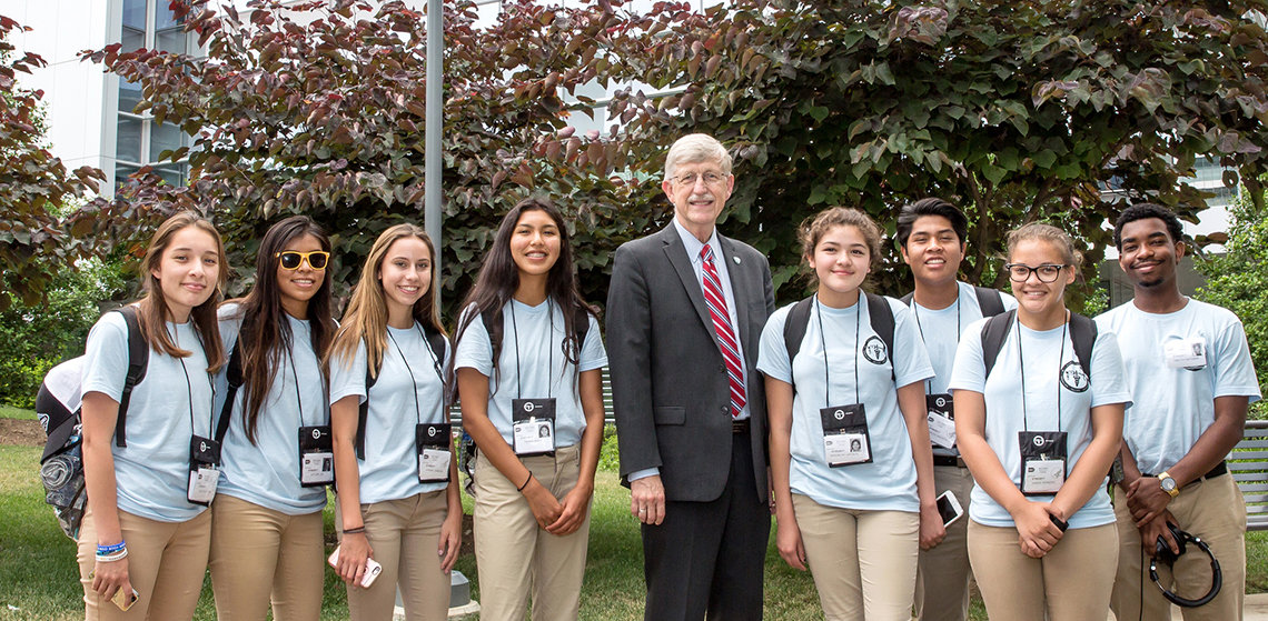 American Indian high school students pose with Dr. Collins outside, on the NIH campus.
