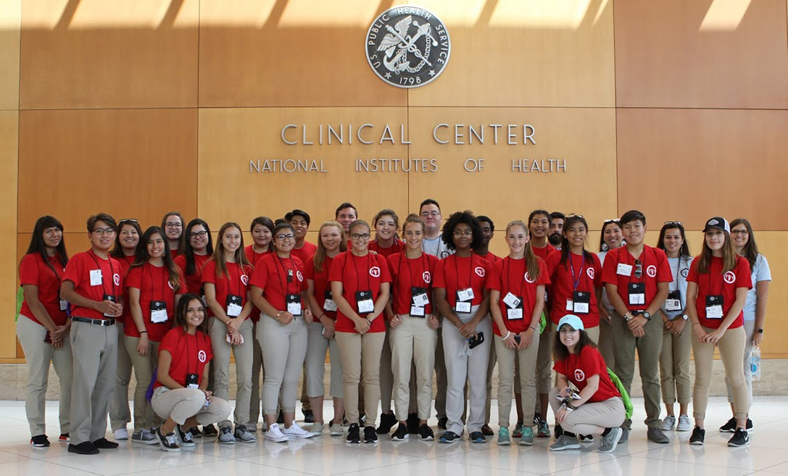 A large group of high school students, dressed in red, pose in the Clinical Center's south lobby.