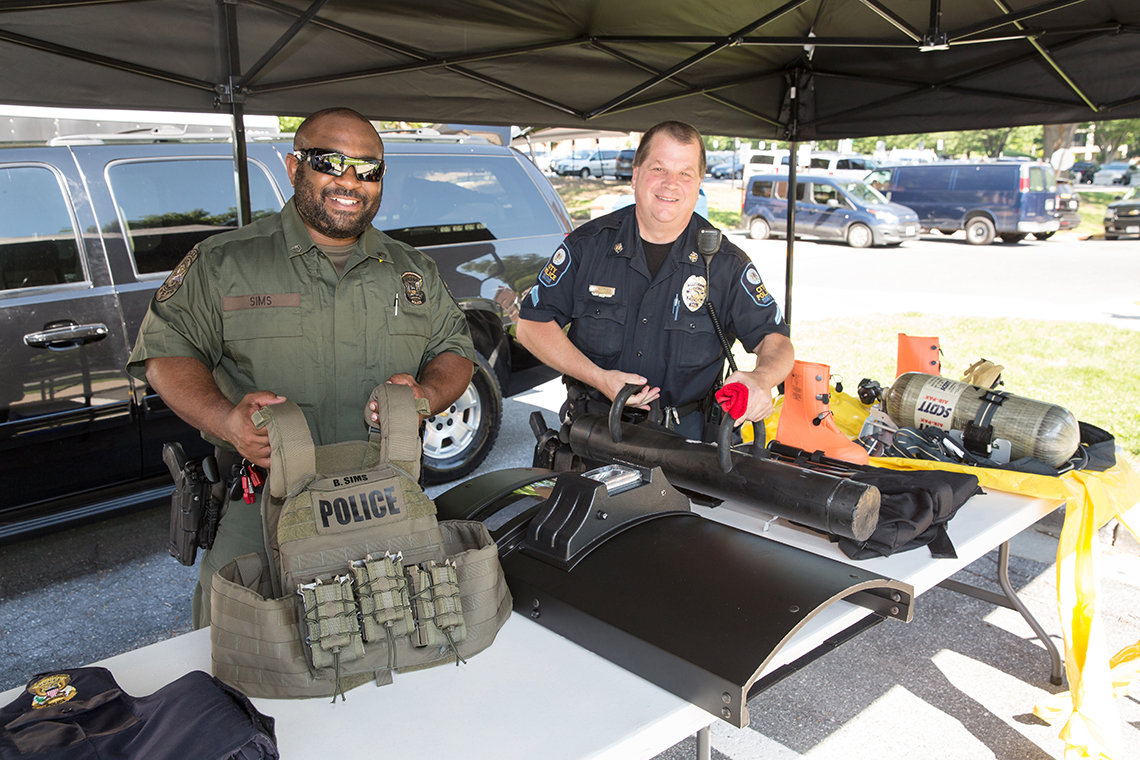 Behind a table, Sims and Matney display some tactical gear.