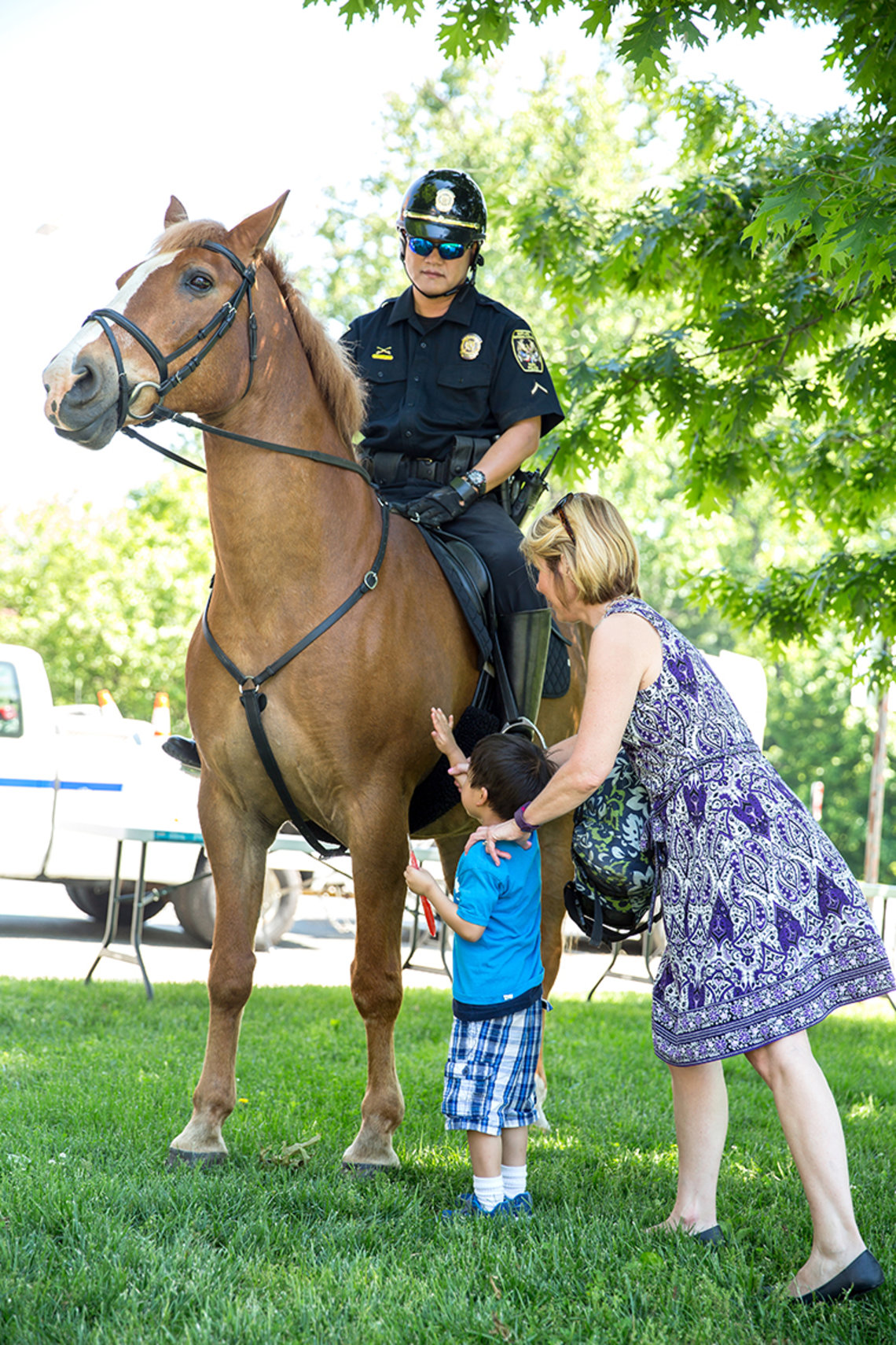 A horse with officer riding is petted by a youngster and adult.