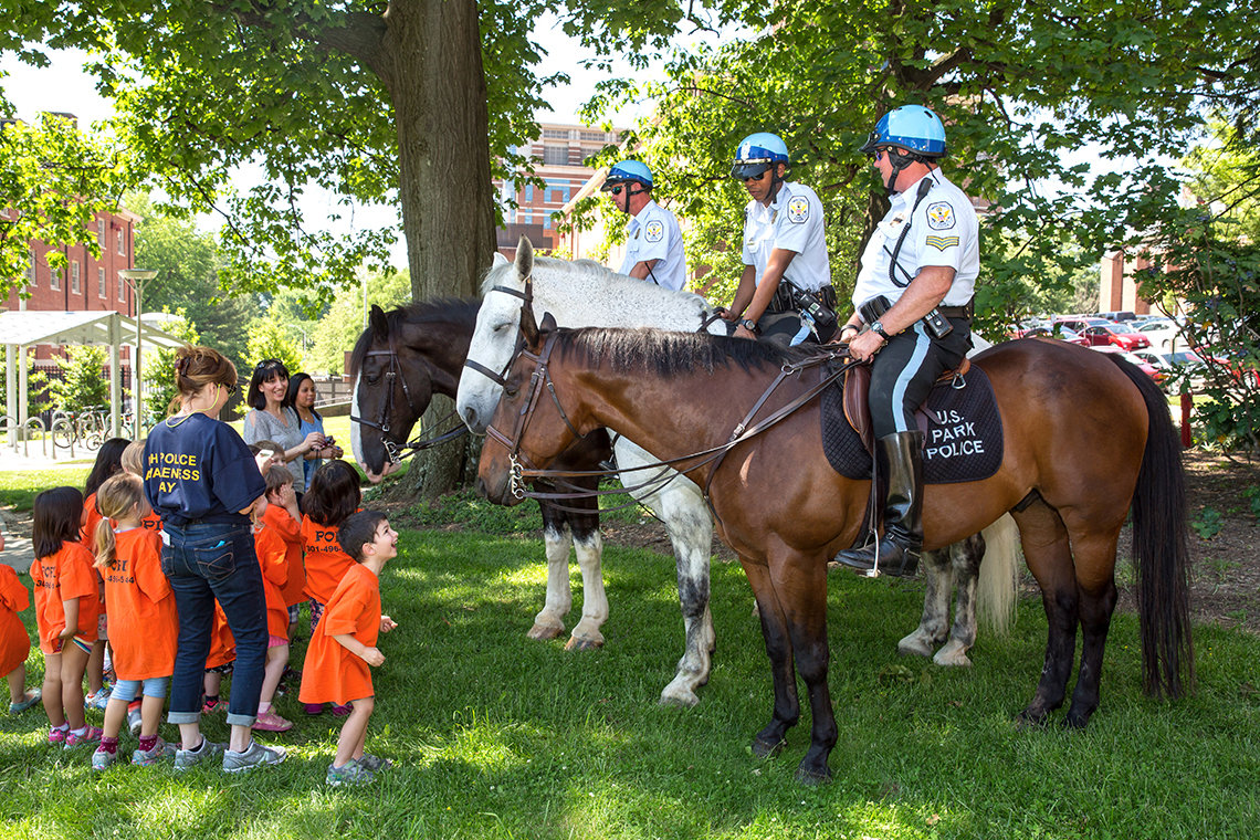 Young children approach officers on horseback.