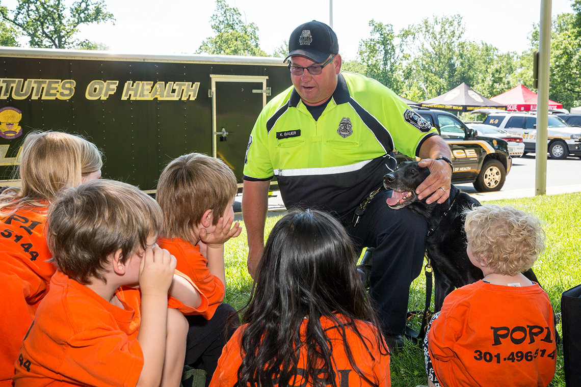 With his hand around a police dog, Bauer talks to several youngsters.